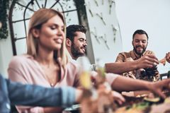 Good food and good friends. Group of young people in casual clothing eating and smiling while having a dinner party indoors royalty free stock photos