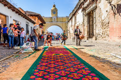 Good Friday carpet & arch, Antigua, Guatemala. Antigua, Guatemala -  March 25, 2016: Locals make dyed sawdust Good Friday carpet in popular street with arch Royalty Free Stock Photography
