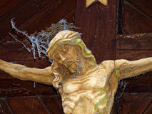 Jesus sculpture on cross in pain with frosted fir needles. Jesus Christ suffering on the cross. Wooden sculpture weathered outside with frosted fir needles in Stock Photo