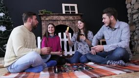 Good friends play in board game with cards on the plaid in a box. Fireplace and Christmas tree background. Company of young friends play in board game with stock video footage