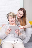 Good fun teaching her grandma to use tablet royalty free stock image