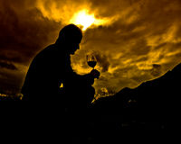 Good glass of wine... Silhouette man thinking in from of a good glass of italian wine stock photos