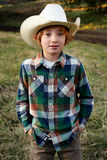 Good Guy White Hat. A little cowboy with a white hat and plaid shirt standing in a field. Shallow depth of field Royalty Free Stock Photography
