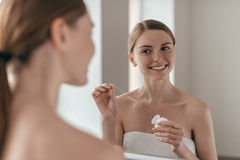 Good habit. Over the shoulder view of young beautiful woman holding dental floss and smiling while looking in the mirror Royalty Free Stock Photography