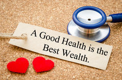 A good health is the best wealth. A good health is the best wealth card and stethoscope with red heart on wood table. Medical concept Stock Photo