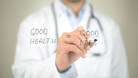 Good Health, Good Life, Doctor writing on transparent screen royalty free stock photo