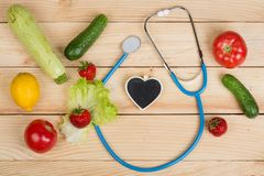Good healthy and diet concept - Blackboard in shape of heart, stethoscope and vegetables, fruits and berries. On wooden table, background, vitamin, care royalty free stock photos