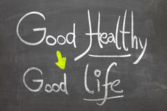 Good Healthy, Good Life in white chalk handwriting on the blackboard Stock Image