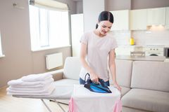 Good house keeper stands in studio apartment and irons clothes. The iron is blue. She is doing that careful. Good house keeper stands in studio apartment and stock images