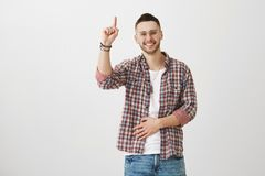 Good ideas come suddenly. Studio shot of handsome young man with bristle, in trendy eyewear raising index finger as if. Pointing up or having proposal to say Royalty Free Stock Photo
