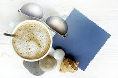 Good impression from vacation with a cup of coffee. Flat lay frothy coffee with sunglasses, sea stones and shells / good impression from vacation with a cup of Stock Photography