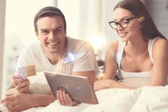 Inventive clever couple purchasing things together. Good investment. Enthusiastic smart nice spouses using credit card paying for things they choose online Royalty Free Stock Images