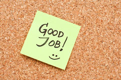 Good job note. Yellow sticky note on an office cork bulletin board with Good job - motivating note royalty free stock photos