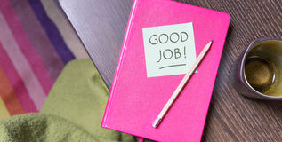 Good Job. Pink notebook, pen and note with the text Good Job Royalty Free Stock Photos