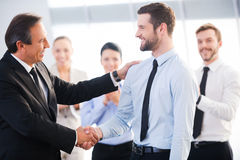 Good job!. Two cheerful business men shaking hands while their colleagues applauding and smiling in the background Royalty Free Stock Photo