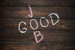 Good Job words written on wooden board over textured wall. Stock Image