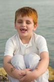 Good joke. Toothless boy laughing while sitting on a sea shore stock photo