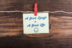 A Good Laugh Equal a good life. Write in sticky note with clothes pin and rope on wood Stock Photography