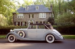 The Good Life. Photo of vintage Rolls Royce automobile parked in front of luxurious home Stock Photography