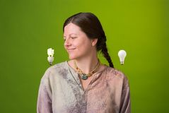 Good light bulb. An environmentalist looks approvingly at a compact fluorescent light bulb Stock Photos