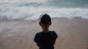 A good little guy dressed in dark clothes and a cap, stand on the seafront and looks at the turbulent Adriatic sea stock footage