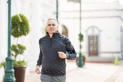 Active mature man jogging in the city. Good looking and active mature man going for a run in the city and exercising Stock Photos