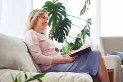 Good-looking adult female smiling while reading book Stock Photos