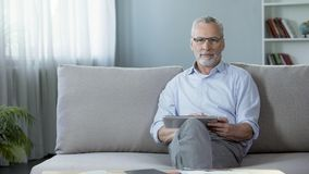 Good-looking adult man sitting on sofa and scrolling on tablet, application Stock Photography