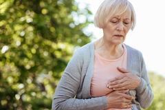 Good looking aged woman having heart attack outdoors. Problems with my heart . Retired helpless ill woman touching her chest and expressing disturbance while Stock Photo