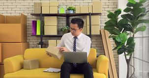 Asian man checking product stock. Good looking Asian black hair man in white shirt and tie using notebook and checking product stock in product store stock video footage