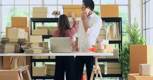 Asian couple checking stock in product store. Good looking Asian couple, man in white shirt using computer and talk to cellphone, woman checking product stock stock footage