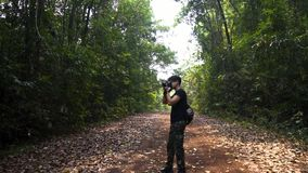 Good looking asian guy standing and take a picture of tropical forest. fresh air. Good looking asian guy standing and take a picture of tropical forest stock video footage