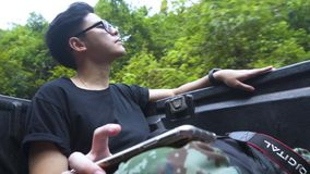 Good looking asian guy tapping for the beat of the song he listen in the forest. Focus at face. Good looking asian guy tapping for the beat of the song he stock footage