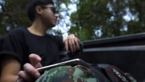 Good looking asian guy tapping for the beat of the song he listen in the forest. Focus at hand. Good looking asian guy tapping for the beat of the song he stock video