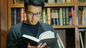Good looking Asian man in glasses reading a book in the library. stock video