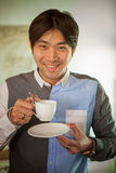 Good looking asian man toothy smiling face happiness emotion wit. H hot coffee cup ready to drink in hand Stock Photography