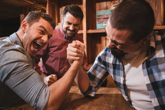 Good looking attractive men confronting each other. Armwrestling match. Good looking attractive brutal men holding their hands together and armwrestling while Stock Photo