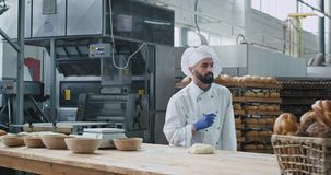 Good looking baker very funny at his work in a big bakery industry dancing and making funny faces while working with. Dough stock video