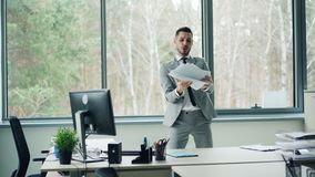 Good-looking bearded man in suit is dancing in office room alone moving body and arms then taking papers from desk and stock video