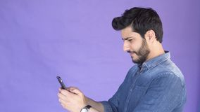 Man texts message on phone. Good-looking bearded man texting a message on phone, wearing denim blue shirt, isolated shot in the purple background stock video footage