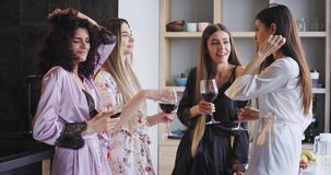 Good looking beautiful ladies dancing in pajamas with a great mood they drinking some wine and enjoying the bachelorette. Party in a modern studio apartment stock footage