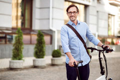 Good looking bespectacled man standing in the street. Happy ride. Handsome bespectacled man smiling and keeping bike while standing in the street Royalty Free Stock Photo