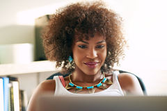 Good-looking black girl looking at desk-top. Young pretty afro-american woman looking at desk-top and smiling on blurred inside background Royalty Free Stock Image