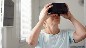 Good-looking blond senior woman in white using VR 360 glasses at home. Active modern elderly people. Good-looking blond senior woman in white putting on and stock footage