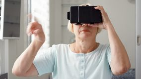 Blond senior woman in white using VR 360 glasses at home. Making browse, zoom and tap gestures stock video