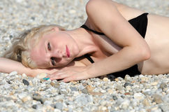 Good looking blonde lady lying on the pebbles beach Stock Photos