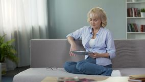 Good-looking blonde senior woman sitting on sofa and scrolling on tablet, apps
