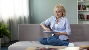 Good-looking blonde senior woman sitting on sofa and scrolling on tablet, apps. Stock photo stock image