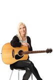Good looking blonde singer songwriter. Young singer-songwriter sitting down with an acoustic guitar. White background Stock Image