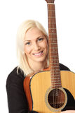 Good looking blonde singer songwriter. Young singer-songwriter sitting down with an acoustic guitar. White background royalty free stock photo
